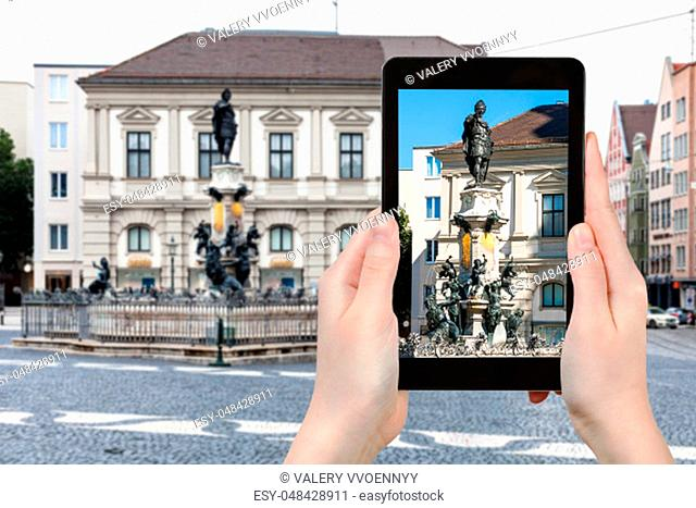 travel concept - tourist photographs of Augustusbrunnen (Augustus) fountain on Rathausplatz square in Augsburg city in Germany on smartphone