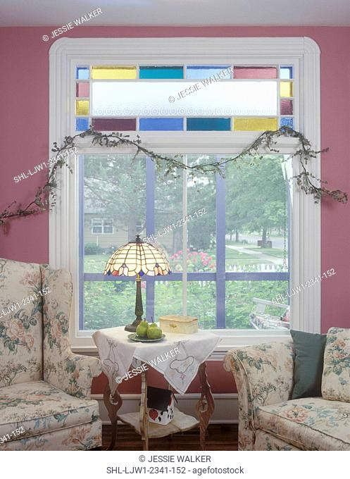 SITTING ROOMS: Family room detail of stained glass window with frosted and colored panes, faux vine, white molding pink walls