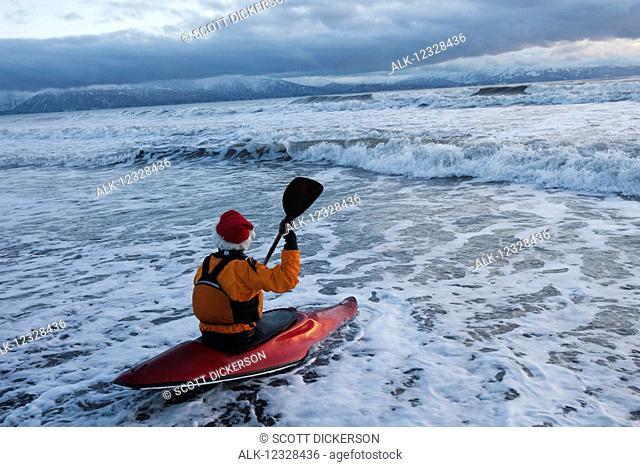 Kayak surfer entering the surf in Kachemak Bay, South-central Alaska, Homer, Alaska, United States of America