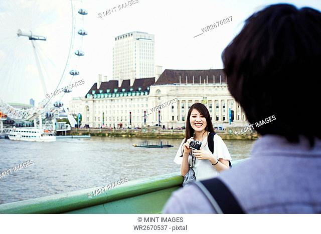 Young Japanese man and woman enjoying a day out in London, standing by the River Thames, London Eye in the background