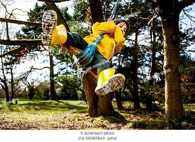 Boy in yellow anorak swinging from park tree
