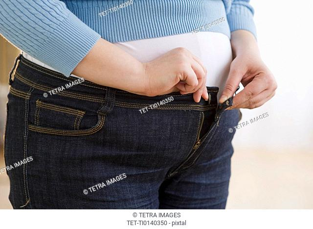 Overweight woman buttoning up her jeans