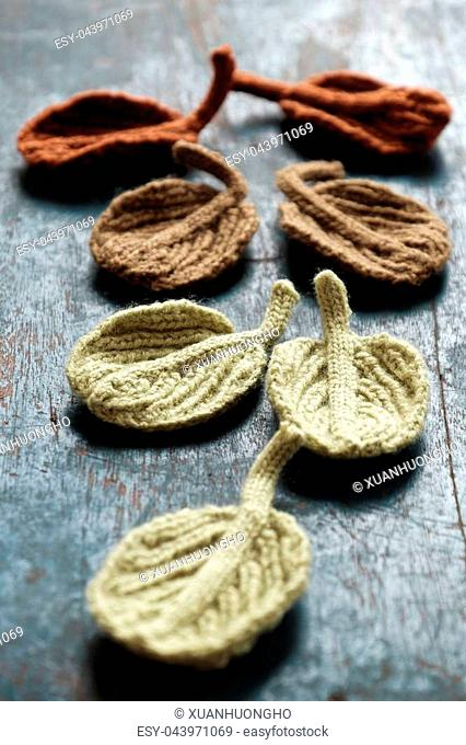 Amazing craft products from yarn, group knitted winter leaf on wooden background, beauty alder leaf with vintage tone