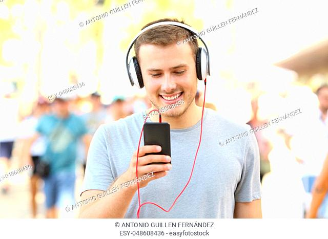 Front view portrait of a happy boy listening to music holding a smart phone and walking on the street