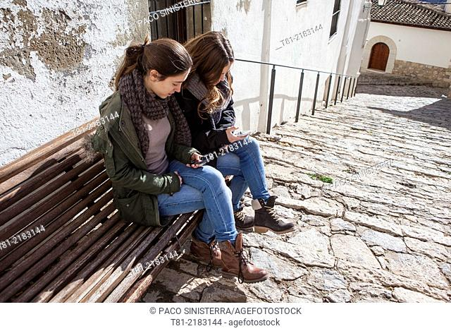 Teenagers talking on the phone in Morella, Castellón, Valencia, Spain