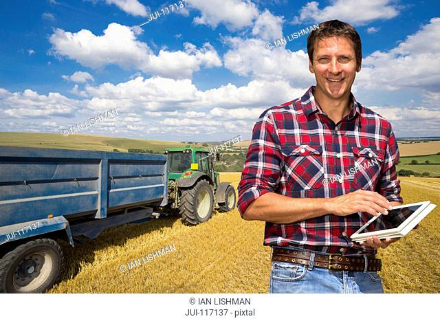 Farmer With Digital Tablet Stands In Wheat Field At Harvest