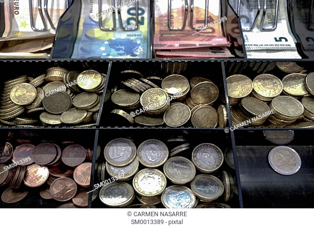 Cash register with euro coins and banknotes in a store