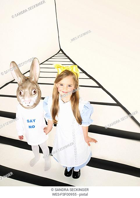 Portrait of smiling little girl dressed up as Alice in Wonderland hand in hand with girl with rabbit mask
