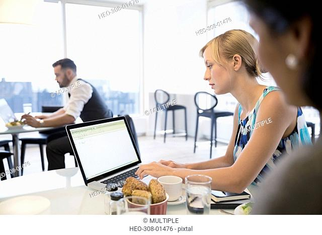 Businesswoman using laptop eating lunch in office cafeteria