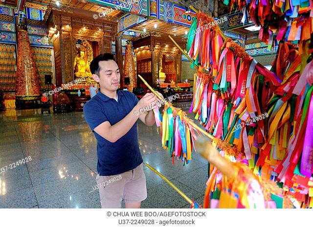 Worshipper making a wish at Kek Lok Si temple, Penang, Malaysia
