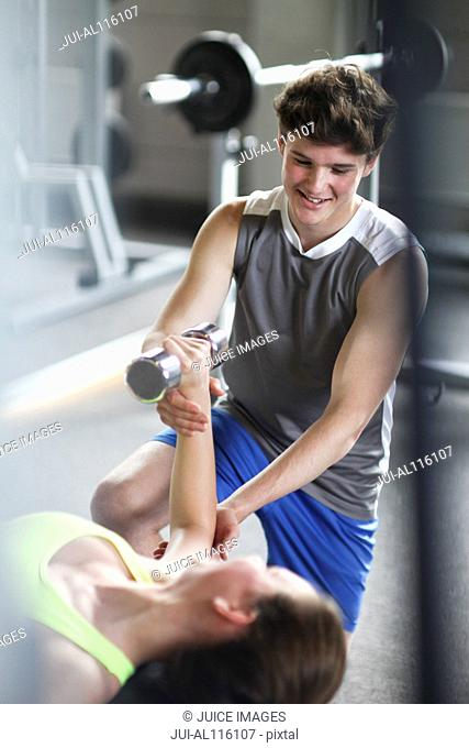 Teenage girl bench pressing with dumb bells in gym