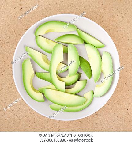 Fresh sliced avocado on plate, over wooden background