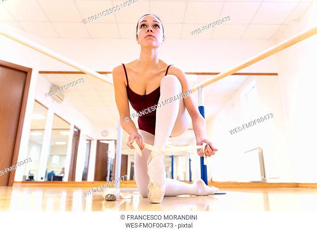 Ballet dancer putting on shoes