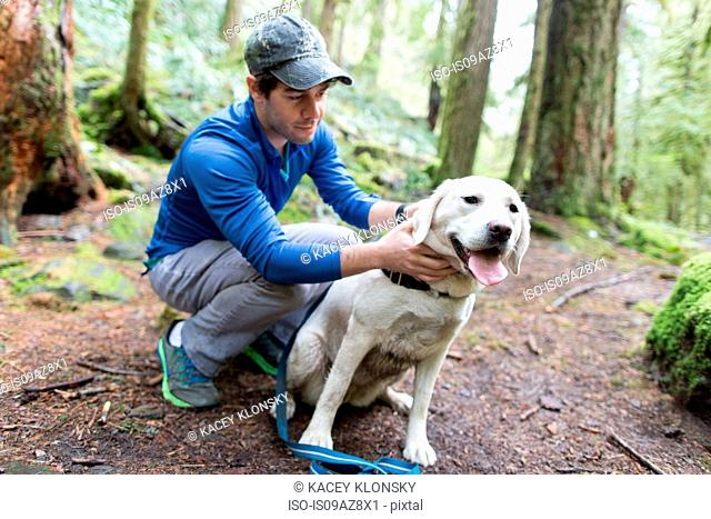 Man crouching in forest stroking dog