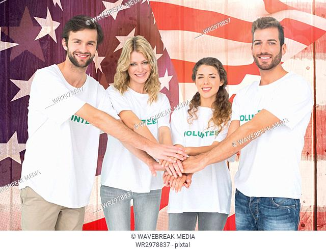 Smiling friends putting their hands together against american flag