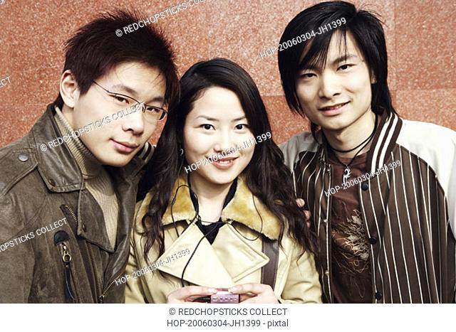 Portrait of a young woman and two young men smiling