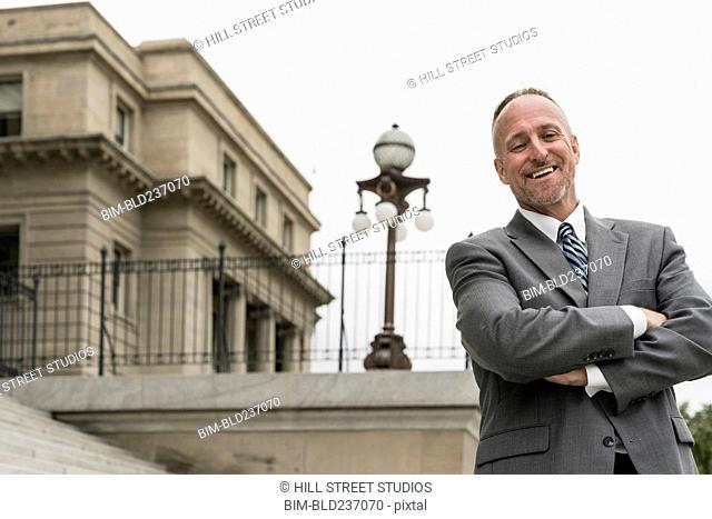 Smiling Caucasian businessman posing outdoors