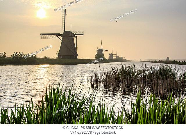 Morning sun just risen shines in the canal where windmills are reflected Kinderdijk Rotterdam South Holland Netherlands Europe
