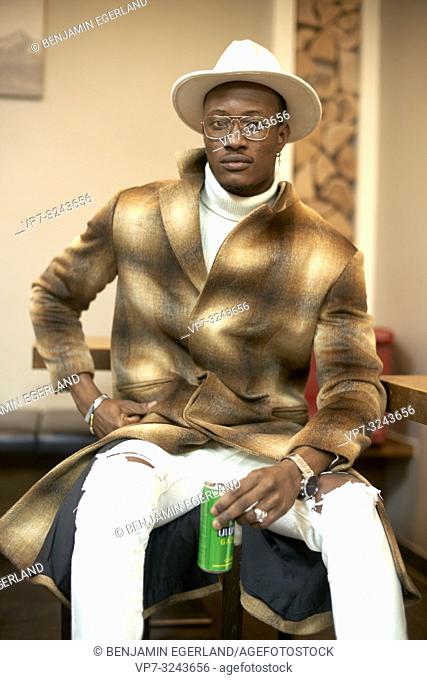 stylish male fashion blogger man sitting indoors, men's style outfit, holding energy drink in hands, in Munich, Germany