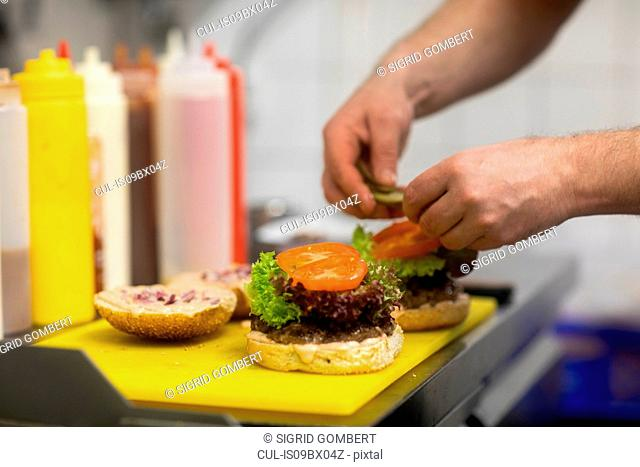 Fast food worker adding salad to hamburger in commercial kitchen, close up of hand