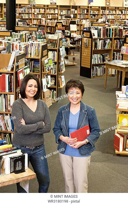 Portrait of Caucasian female and Asian American female owners of a large bookstore, showing multiple racks of books in the background