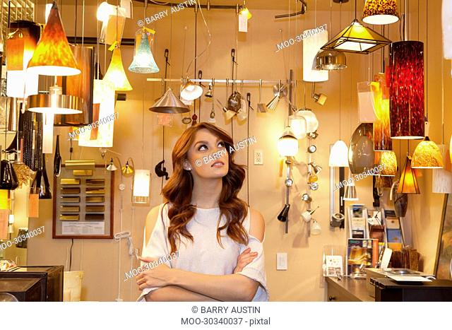 Beautiful young woman browsing for lights with arms crossed in store