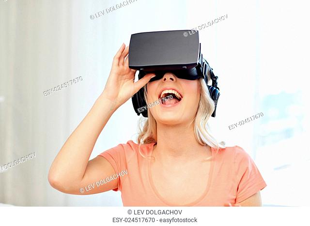 technology, virtual reality, cyberspace, entertainment and people concept - happy amazed young woman in virtual reality headset or 3d glasses and headphones at...