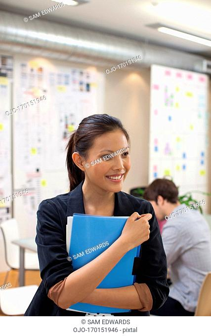 Portrait of smiling businesswoman with folders in office