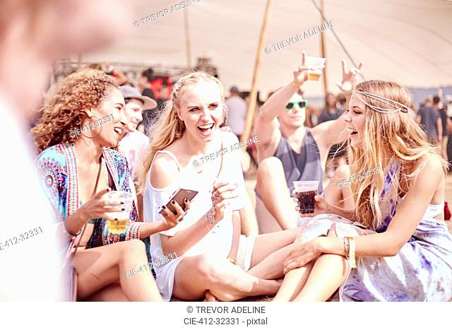 Young women hanging out drinking at sunny music festival