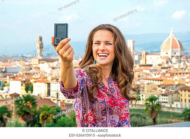 Happy young woman making selfie against panoramic view of florence, italy