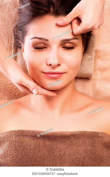 eautiful young relaxed woman enjoy receiving face massage at spa saloon