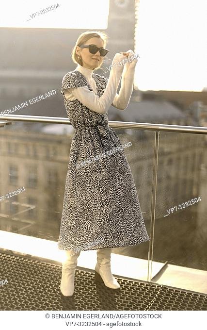 well-dressed fashionable blogger woman on balcony in city Munich, Bavaria, Germany