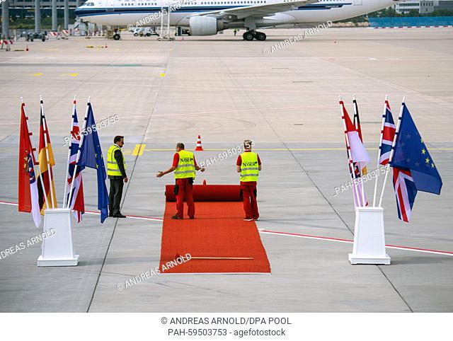 Employees roll out the red carpet for the arrival of the British Queen Elizabeth IIat the airport in Frankfurt am Main, Germany, 25 June 2015