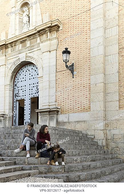 Mother and daughters sitting on the stairs next to the Church of Altea, province of Alicante, Spain