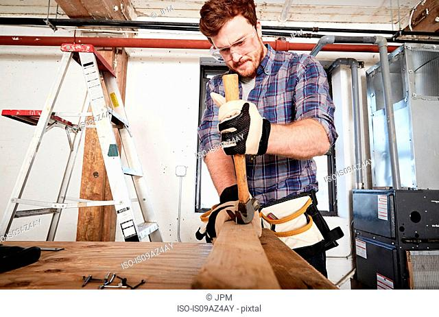 Carpenter in workshop removing nails form timber using hammer