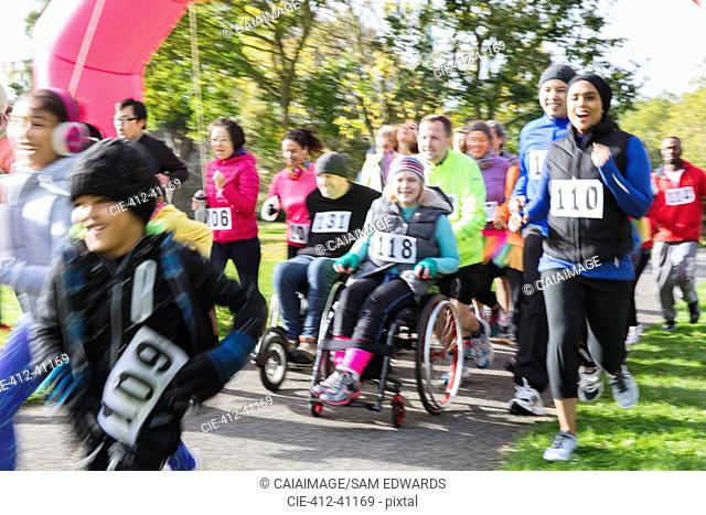 Runners and people in wheelchairs at charity run in park