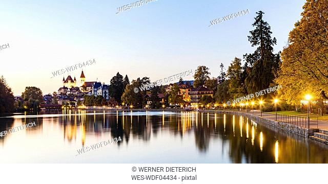 Switzerland, Canton of Bern, Thun, river Aare, old town with Aarequai, parish church and castle at dusk