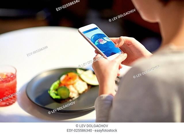 food, new nordic cuisine, technology and people concept - close up of woman with smartphone photographing toast skagen with shrimps, lemon mayonnaise
