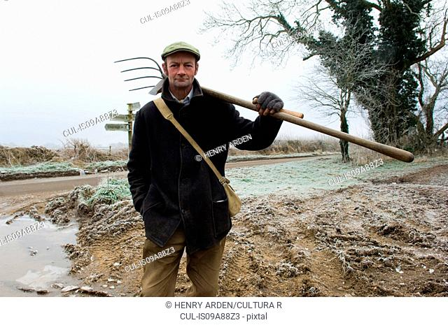 Portrait of mature farmer holding pitchfork