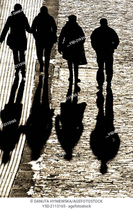 people walking paved street with long shadows, view from above