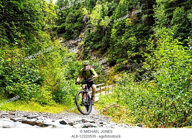 A man riding a mountain bike struggles up a hill on the Johnson Pass Trail in Southcentral Alaska, USA
