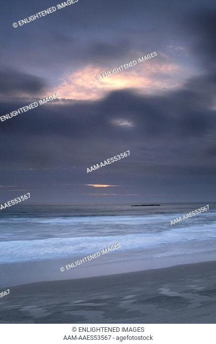 Wind blowing dark clouds at sunet and ocean wave surf breaking on sand Beverly Beach State Park, near Newport, Oregon