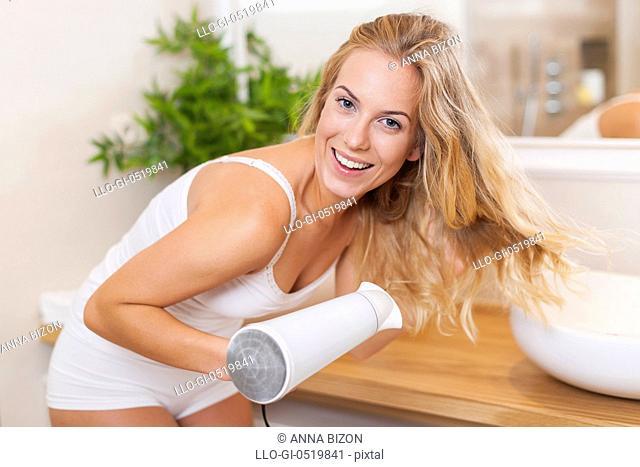 Portrait of beautiful blonde woman drying hair in bathroom. Debica, Poland