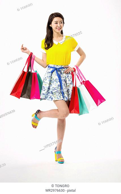 Young smiling woman posing with shopping bags