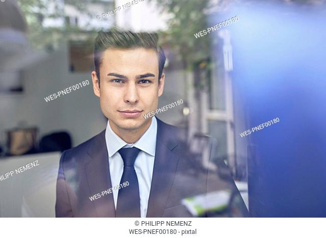 Young businessman behind glass pane in office