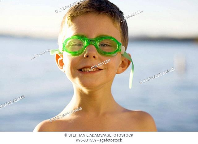 Happy boy about to swim wearing goggles