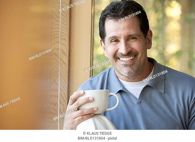 Hispanic man having cup of coffee