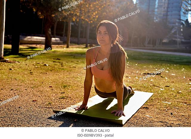 Woman practising yoga in city park, Barcelona, Catalonia, Spain