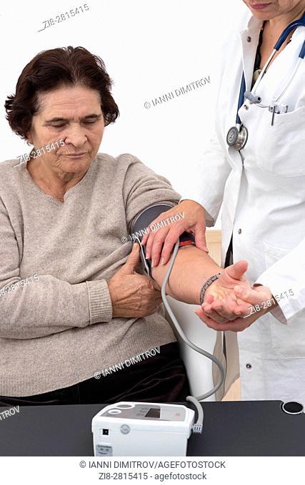Doctor checks blood pressure of senior female patient