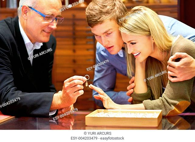 Mature jewellery store clerk assisting a couple in choosing an engagement ring